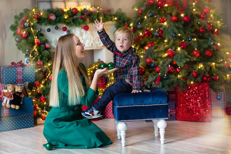 Portrait of happy mother and adorable baby celebrate Christmas. New Year`s holidays. Toddler with mom in the festively decorated stock photography