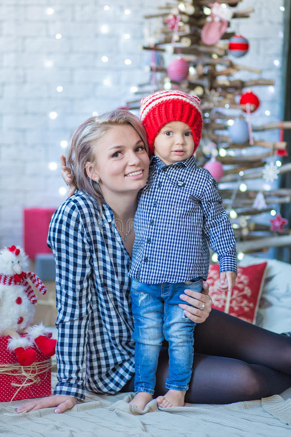 Portrait of happy mother and adorable baby celebrate Christmas. New Year`s holidays. Toddler with mom in the festively decorated r stock photography