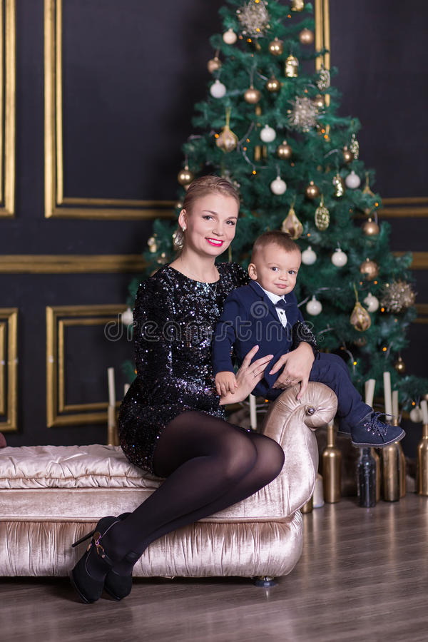 Portrait of happy mother and adorable baby celebrate Christmas. New Year`s holidays. Toddler with mom in the festively decorated r royalty free stock photos