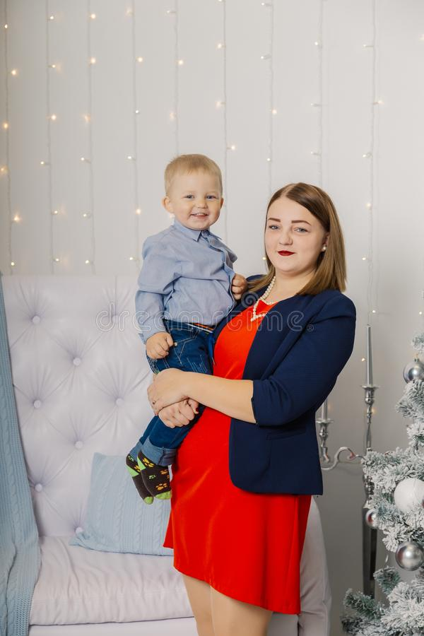Portrait of happy mother and adorable baby celebrate Christmas. New Year`s holidays. Toddler with mom in the festively stock images