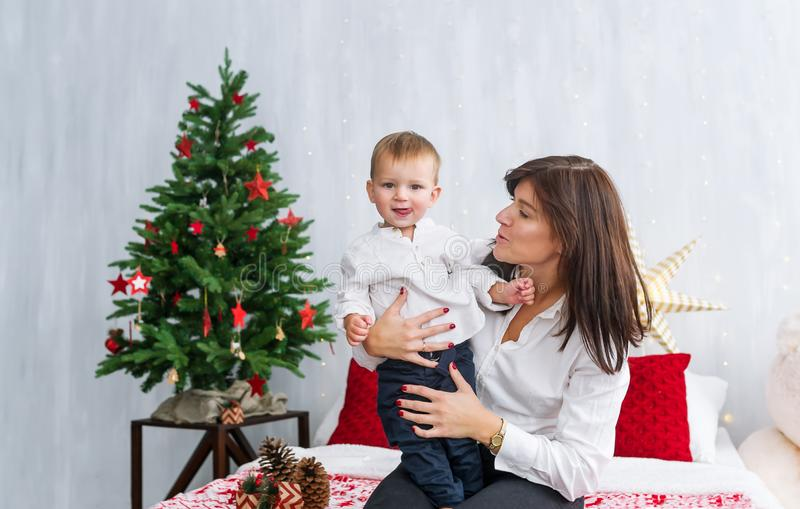Portrait of happy mother and adorable baby son celebrate Christmas stock photos