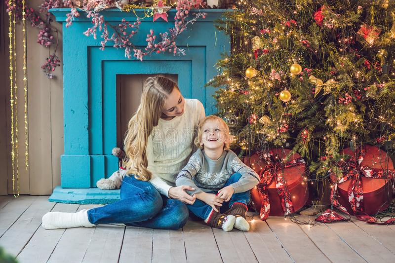 Portrait of happy mother and adorable boy celebrate Christmas. New Year`s holidays. Toddler with mom in the festively decorated r stock photos