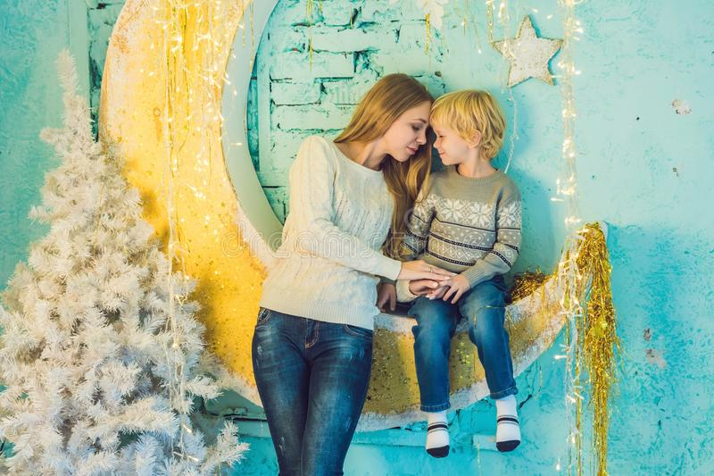 Portrait of happy mother and adorable boy celebrate Christmas. New Year`s holidays. Toddler with mom in the festively decorated r stock image