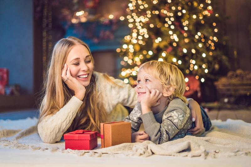 Portrait of happy mother and adorable boy celebrate Christmas. New Year`s holidays. Toddler with mom in the festively decorated r royalty free stock photo