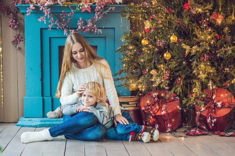 Portrait of happy mother and adorable boy celebrate Christmas. New Year`s holidays. Toddler with mom in the festively decorated r stock photo