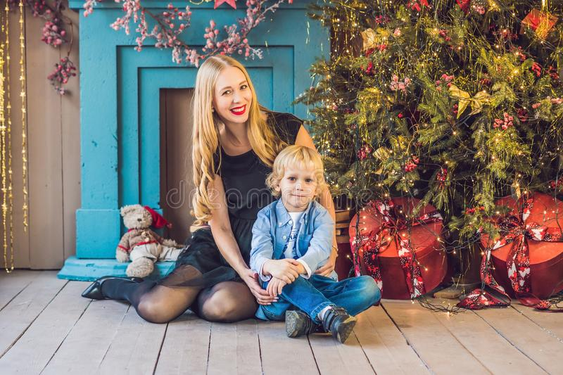 Portrait of happy mother and adorable boy celebrate Christmas. New Year`s holidays. Toddler with mom in the festively decorated r royalty free stock image
