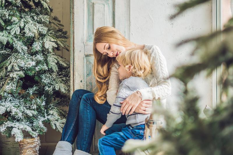 Portrait of happy mother and adorable boy celebrate Christmas. New Year`s holidays. Toddler with mom in the festively decorated r royalty free stock photography