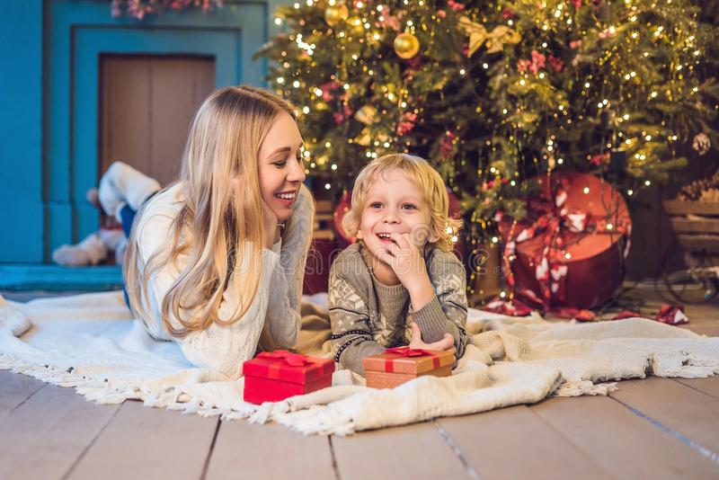 Portrait of happy mother and adorable boy celebrate Christmas. New Year`s holidays. Toddler with mom in the festively decorated r royalty free stock images