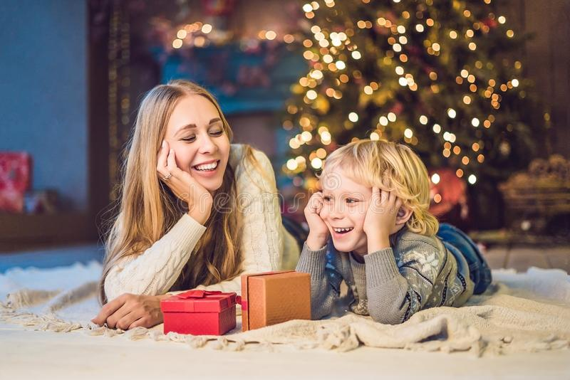 Portrait of happy mother and adorable boy celebrate Christmas. New Year`s holidays. Toddler with mom in the festively decorated r stock images