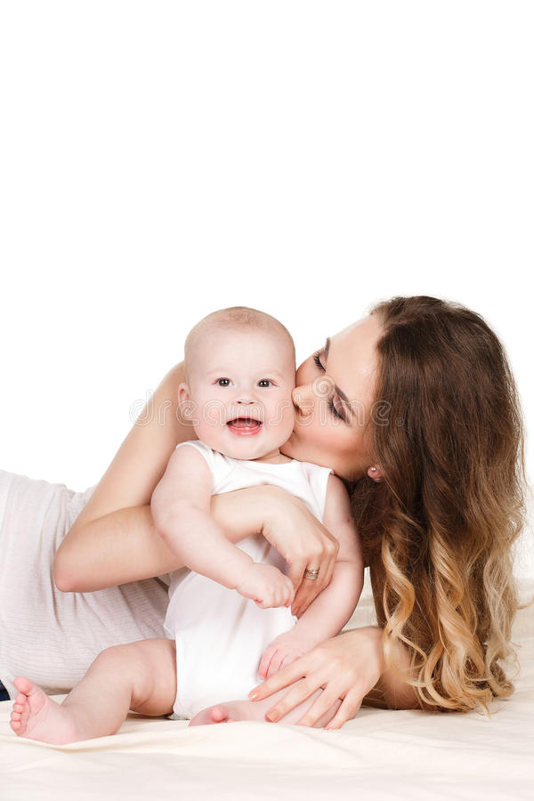 Portrait of happy mother with baby. Portrait of a mother and baby isolated on white background on a light beige blanket,brown-eyed baby with a fluffy short hair stock images