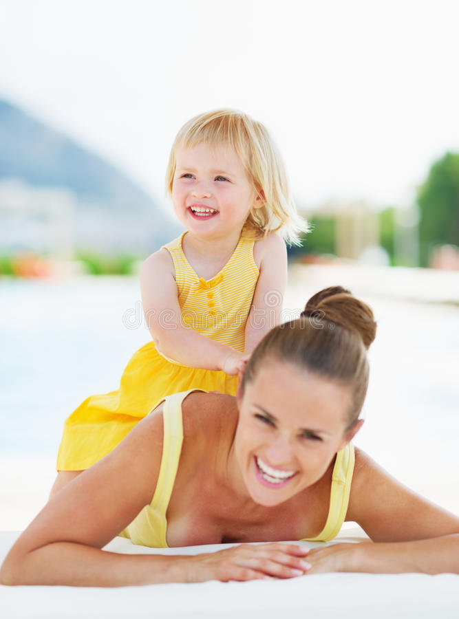Portrait of happy mother and baby at poolside. Portrait of happy young mother and baby girl at poolside stock image