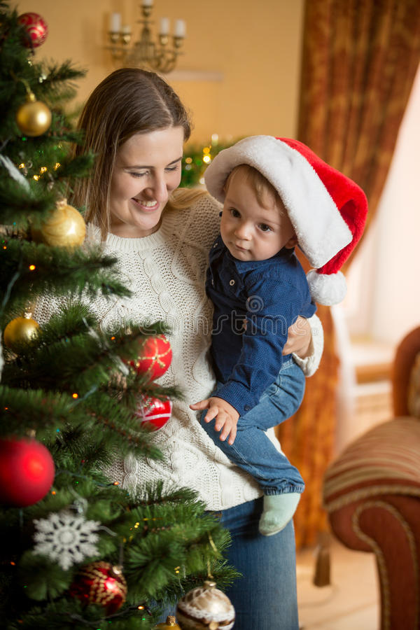 Portrait of happy mother cuddling her baby boy in Santa cap at C stock image