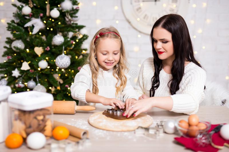 Portrait of happy mother and daughter cooking gingerbreads in kitchen with Christmas tree stock images