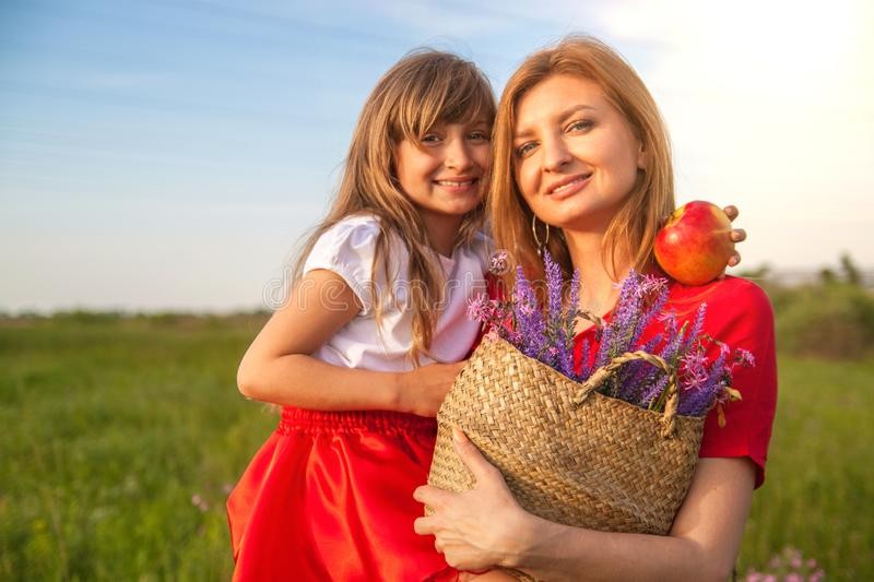 A portrait of Happy mother and daughter in green field in nature in summer. Nature, happiness. stock photo