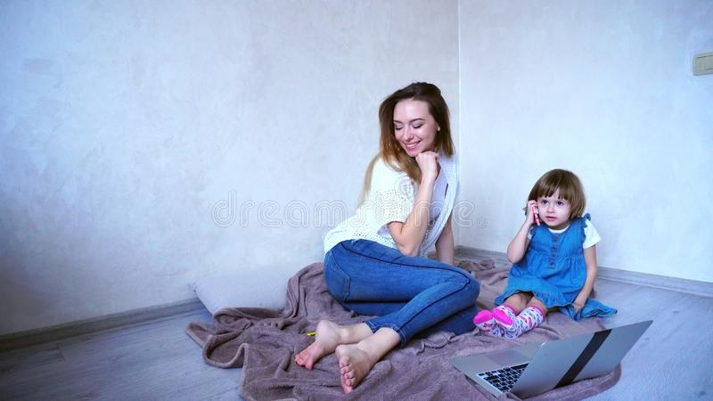 Young female mother and daughter child use gadgets for communica stock photo
