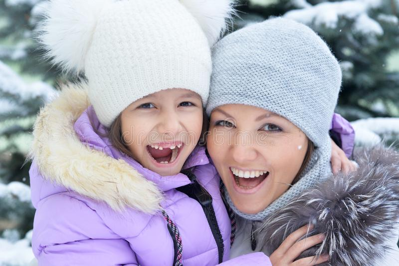 Portrait of happy mother and daughter in winter stock image