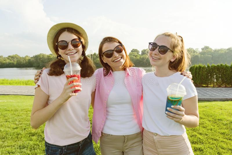 Portrait of happy mother and daughters teenagers 14 and 16 years old, girls with summer drinks. Background nature, recreation area royalty free stock images