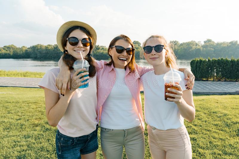 Portrait of happy mother and daughters teenagers 14 and 16 years old, girls with summer drinks. Background nature, recreation area royalty free stock image