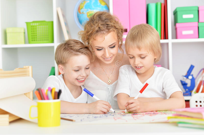 Portrait of happy mother drawing with three sons royalty free stock photo