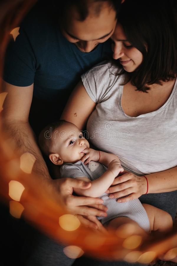 Portrait of happy mother and father holding sweet adorable healthy 4 months child carefully on arms. Chrismas lights royalty free stock photography