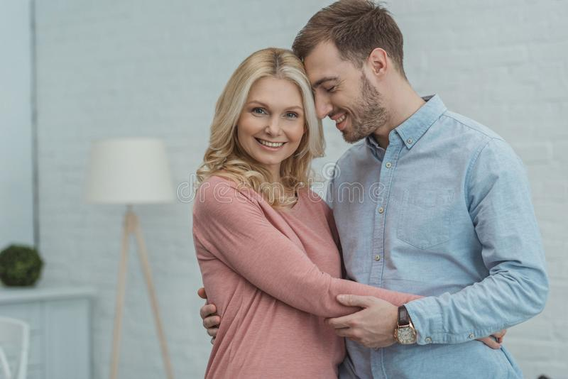 Portrait of happy mother and grown son hugging. Each other stock image