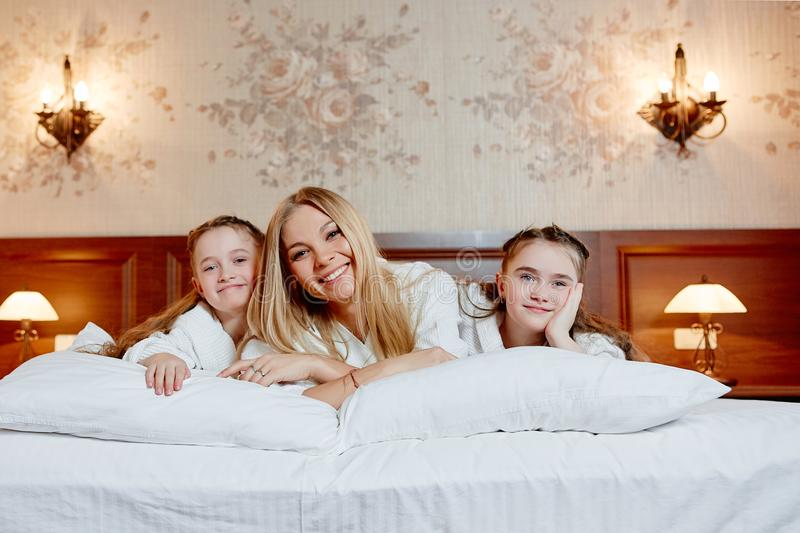 Portrait of a happy mother and her children lying on a bed royalty free stock photos