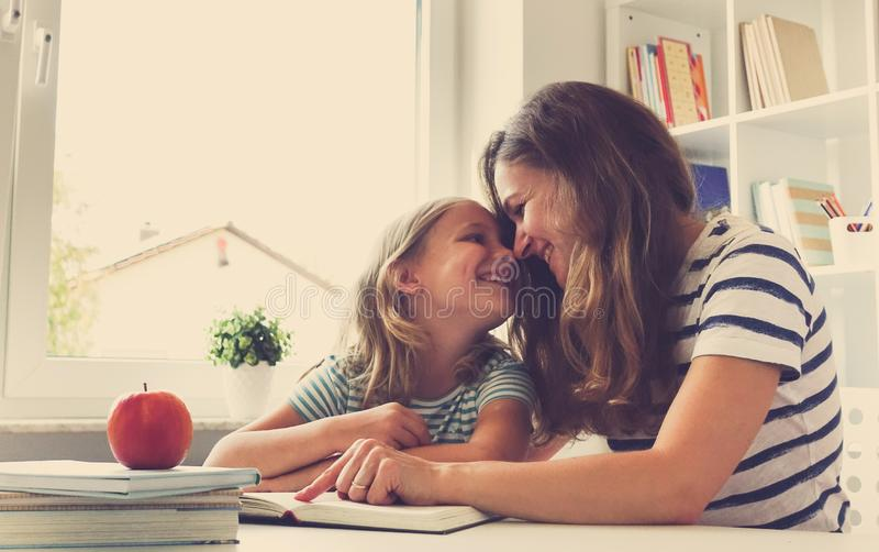 Portrait of happy mother and her pretty little daughter at the t. Portrait of happy young mother and her pretty little daughter sitting at the table and reading royalty free stock photography
