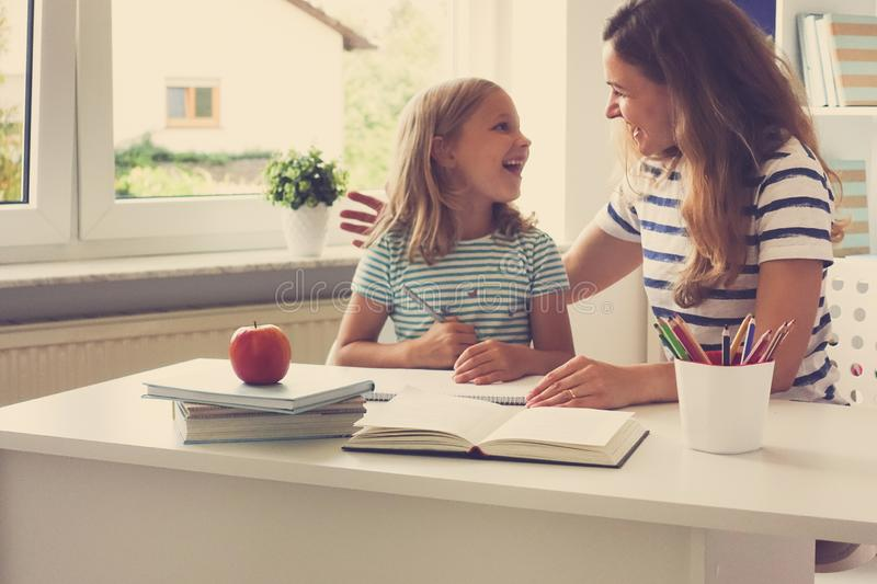 Portrait of happy mother and her pretty little daughter at the t. Portrait of happy young mother and her pretty little daughter sitting at the table and reading stock photography