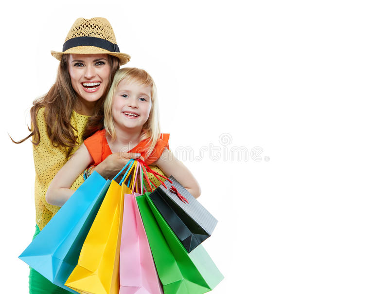 Portrait of happy mother hugging daughter with shopping bags. Colourful vibes of family shopping. Portrait of happy mother hugging daughter with shopping bags on royalty free stock image