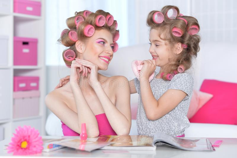 Portrait of happy  Mother and little daughter with hair curlers royalty free stock image