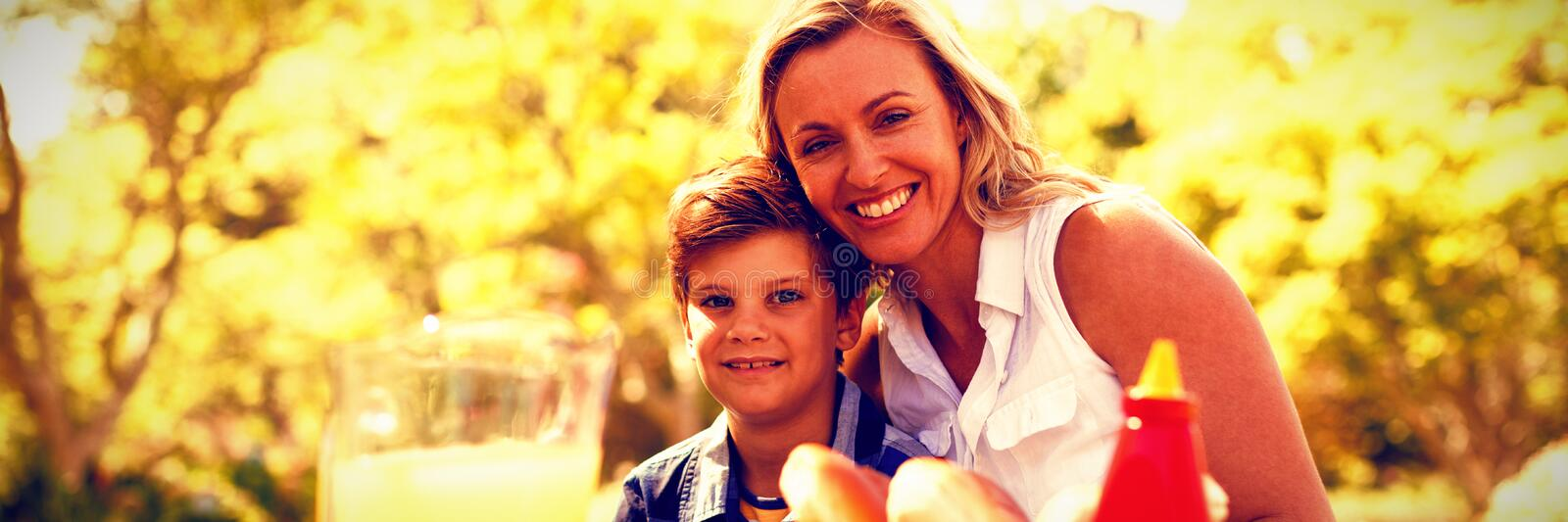 Portrait of happy mother and son having meal in park stock photos