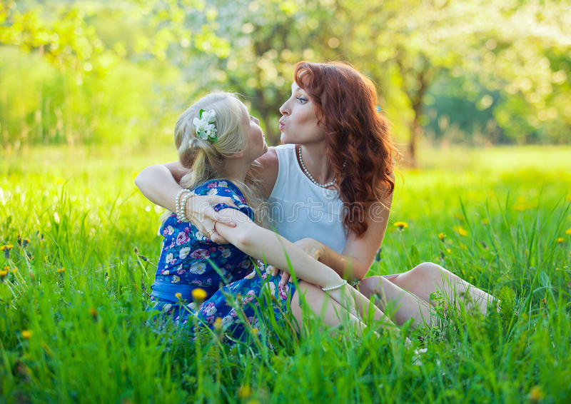 Portrait of happy mother and young daughter with heart in a beautiful blooming fruit garden with white blossoms on apple stock photo