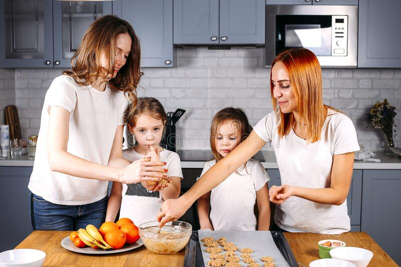Portrait of happy mothers and two daughters cooking. In the kitchen stock photos