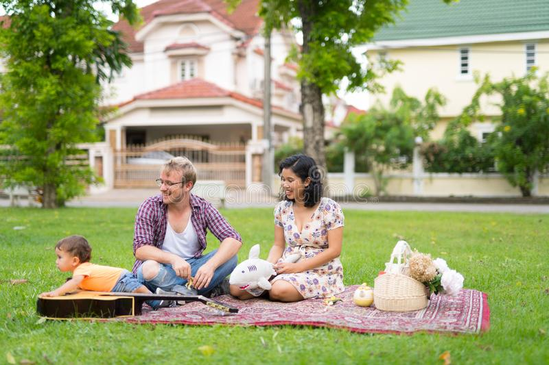 Portrait of happy multi-ethnic family bonding together outdoors stock photo