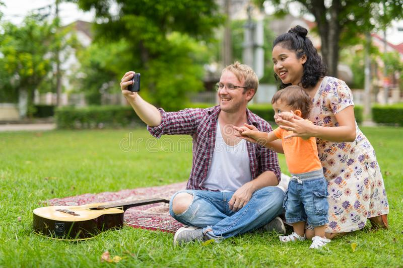 Portrait of happy multi-ethnic family taking selfie together outdoors royalty free stock photos