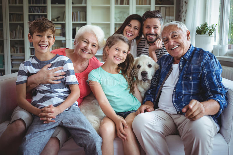 Portrait of happy multi-generation family sitting on sofa in living room royalty free stock photo
