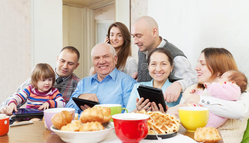 Happy multigeneration family uses electronic devices stock photos