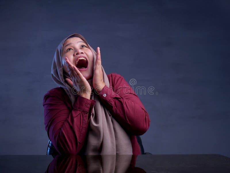 Happy Muslim Woman Shows Winning Gesture Greeting Something. Portrait of happy muslim woman celebrating victory, winning gesture smiling and greeting something stock image