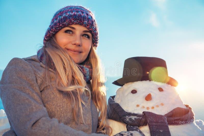 Happy female with snowman stock photos