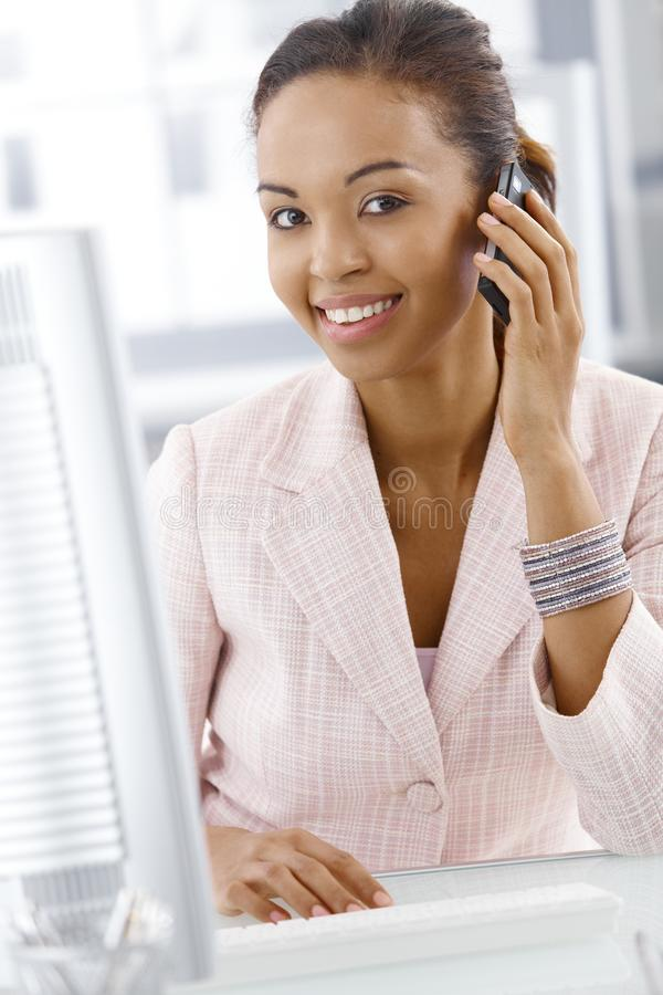 Portrait of happy office worker on phone. Portrait of happy office worker woman on mobile phone call, smiling at camera stock photos