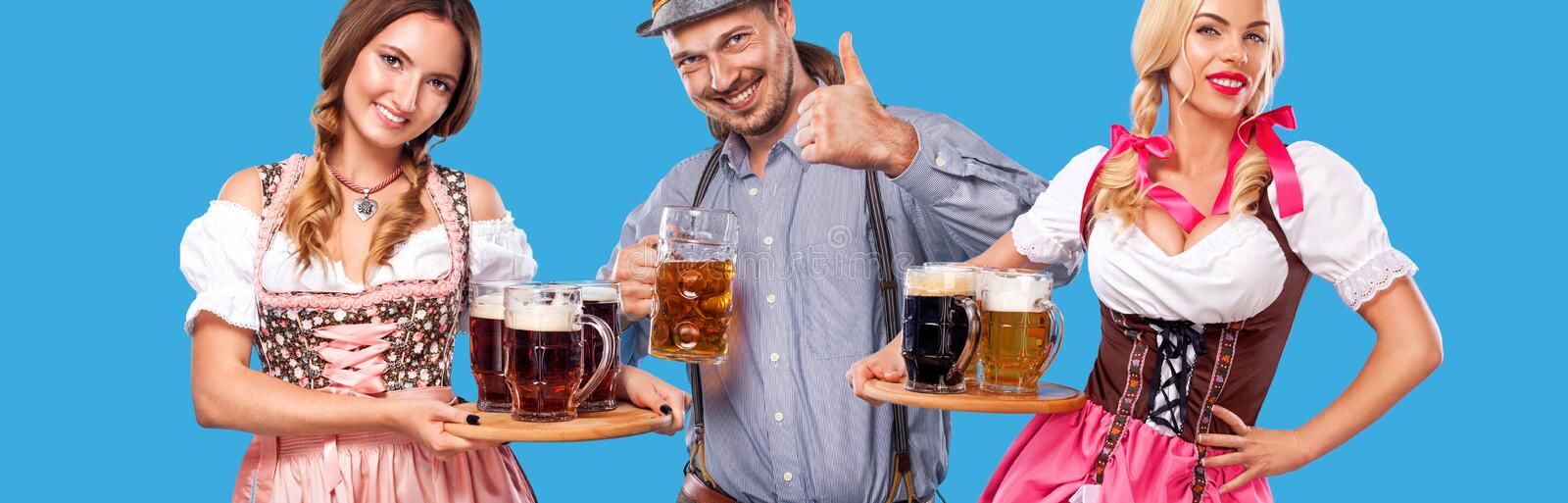 Portrait of happy Oktoberfest man and two women, wearing a traditional Bavarian clothes, serving big beer mugs on blue stock photos