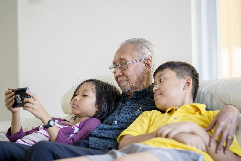 Old man and grandchildren relaxing on sofa. Portrait of happy old men and his grandchildren relaxing on the sofa at home while playing mobile phone together stock photography
