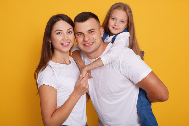 Portrait of happy parents, daddy carries their beautiful daughters on his back. Lovely family of three pose together against royalty free stock photography