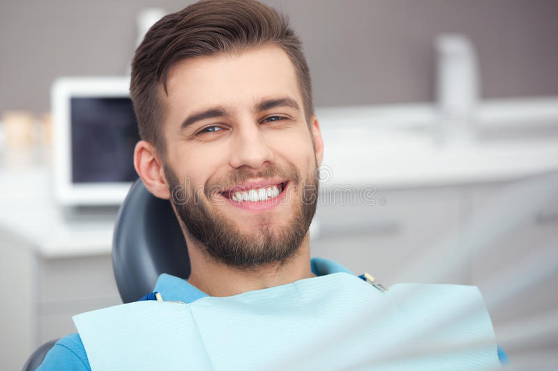 Portrait of happy patient in dental chair. My smile is perfect! Portrait of happy patient in dental chair royalty free stock photos