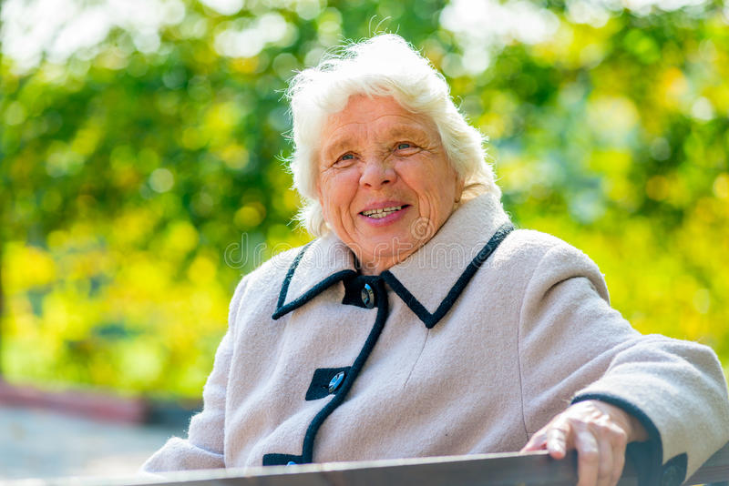 Portrait of happy pensioner sitting on a bench royalty free stock photography