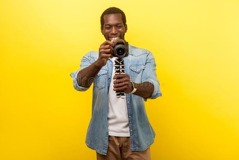 Portrait of happy photographer holding professional digital dslr camera. indoor studio shot isolated on yellow background. Portrait of happy photographer, joyous royalty free stock image