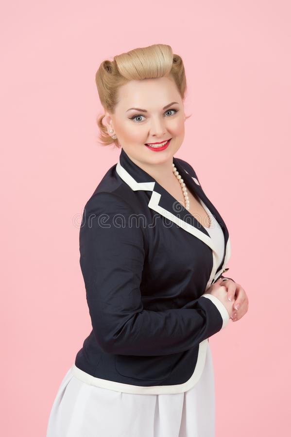Portrait of happy pin-up styled woman with blonde curls. Blonde in blue jacket with pin-up style make-up. royalty free stock photography