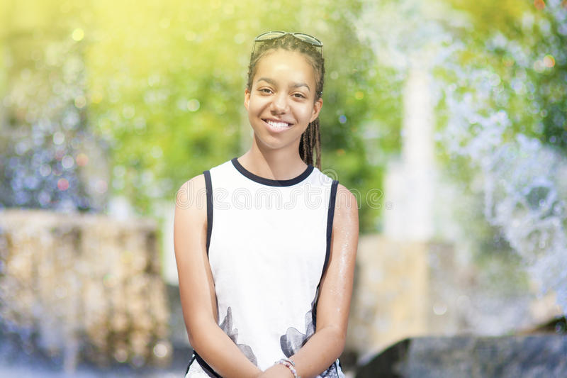 Portrait of Happy Positive African American Teenager Girl. With Long Dreadlocks in Sunglasses. In Front of Fountain Outdoors. Horizontal image Orientation stock photo