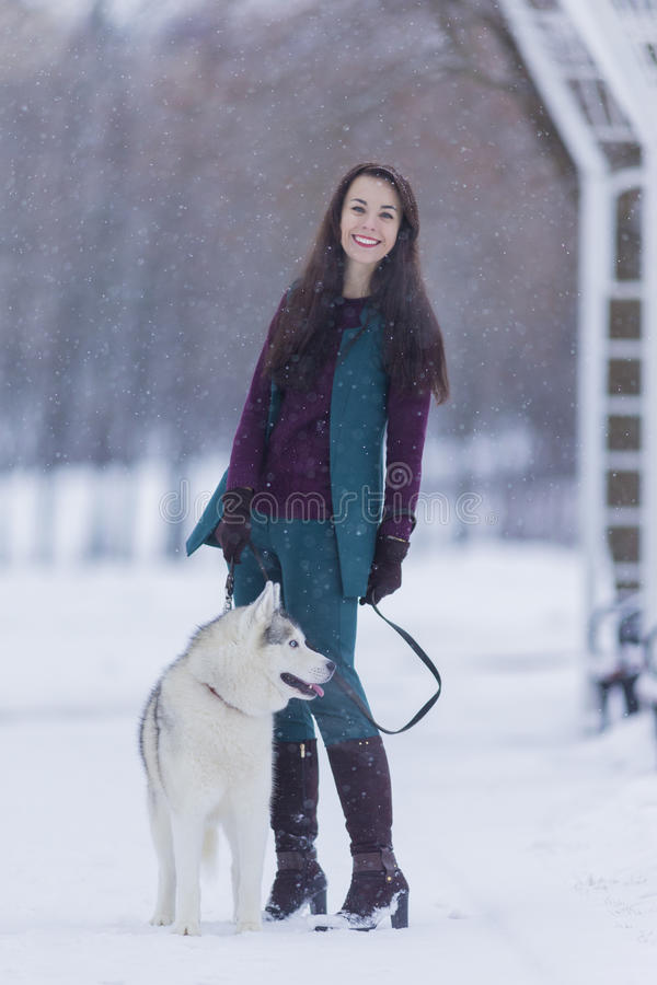 Portrait of Happy Positive Caucasian Brunette Woman Posing With Husky Dog stock images