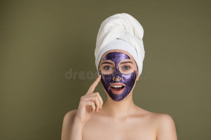 Portrait of a happy and positive naked girl with a purple clay cosmetic mask on her face. Touching her finger to her cheek  on green background stock photos
